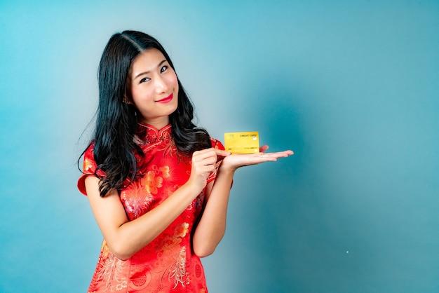 Bella giovane donna asiatica indossa un abito tradizionale cinese rosso con la mano che tiene la carta di credito per mostrare fiducia e sicurezza per effettuare il pagamento sul blu