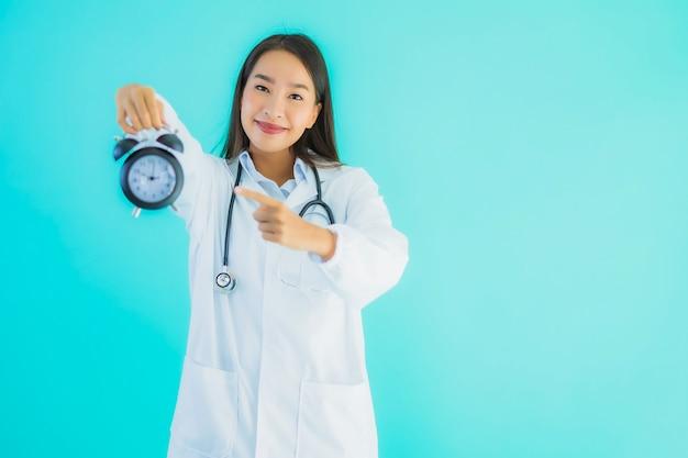Bella giovane donna asiatica medico con orologio o sveglia