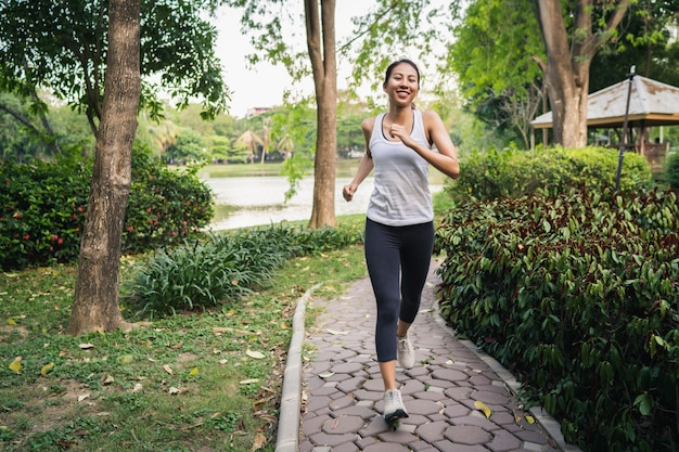 Bella giovane donna asiatica sana del corridore in abbigliamento di sport che corre e che pareggia