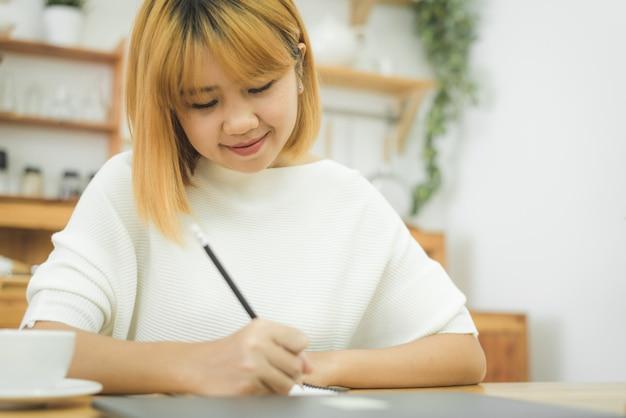 Bella giovane donna asiatica sorridente che lavora al computer portatile mentre sedendosi in un salone a casa