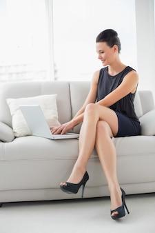 Bella giovane donna ben vestita che utilizza computer portatile sul sofà