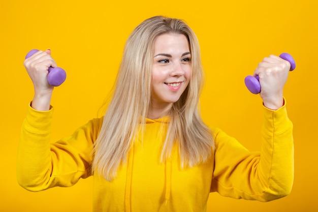 Bella giovane donna bionda allegra in vestiti sportivi gialli casuali che fanno gli esercizi con le piccole teste di legno viola da 0,5 chilogrammi.