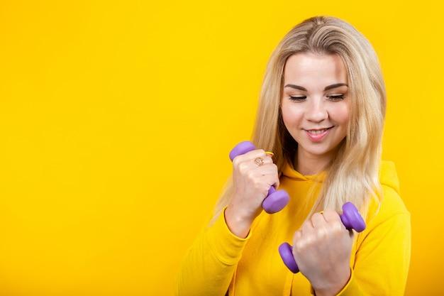 Bella giovane donna bionda attraente in vestiti sportivi gialli casuali che fanno gli esercizi con le piccole teste di legno porpora da 0,5 chilogrammi.