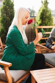 Bella giovane donna bionda che odora rosa rossa