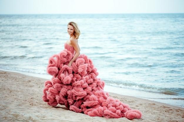 Bella giovane donna bionda che porta vestito rosa sulla spiaggia