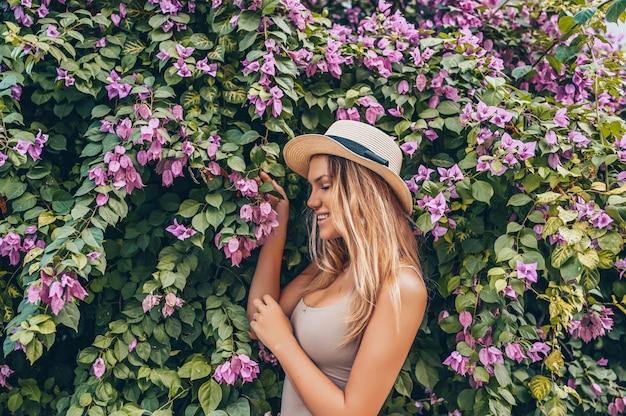 Bella giovane donna bionda che posa con i fiori tropicali