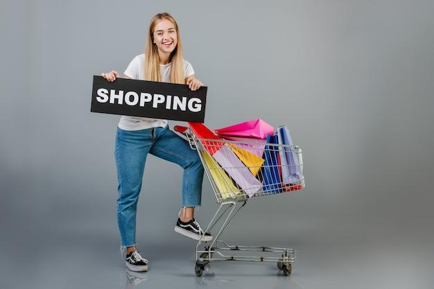 Bella giovane donna bionda con il segno di acquisto e carrello con i sacchetti della spesa variopinti isolati sopra grey
