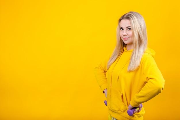 Bella giovane donna bionda felice in vestiti sportivi gialli casuali che fanno gli esercizi con le piccole teste di legno viola da 0,5 chilogrammi.