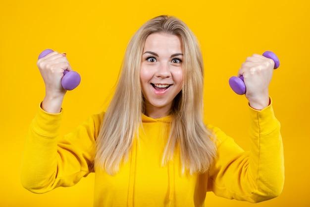 Bella giovane donna bionda pazza in vestiti sportivi gialli casuali che fanno gli esercizi con le piccole teste di legno porpora da 0,5 chilogrammi.