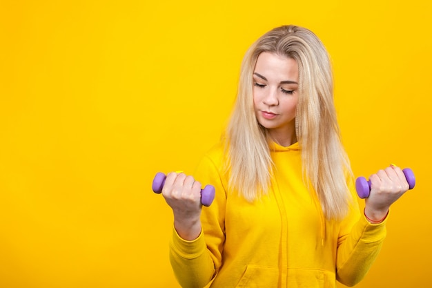Bella giovane donna bionda seria in vestiti sportivi gialli casuali che fanno gli esercizi con le piccole teste di legno viola da 0,5 chilogrammi.