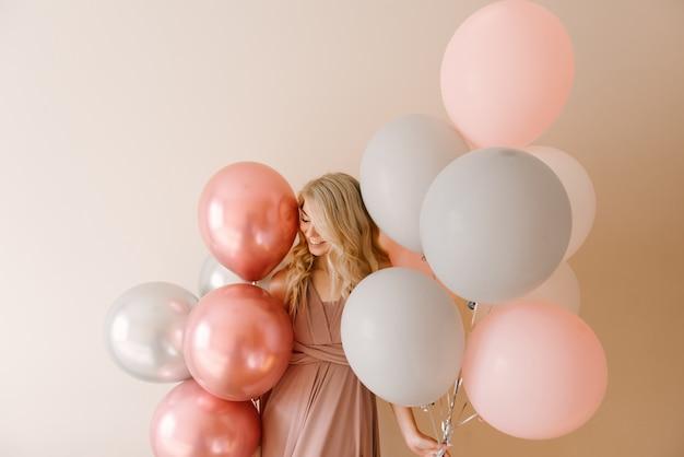 Bella giovane donna bionda sorridente con palloncini bianchi grigi e rosa