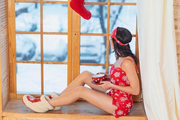 Bella giovane donna castana che indossa il pigiama rosso che si siede a casa dalla finestra