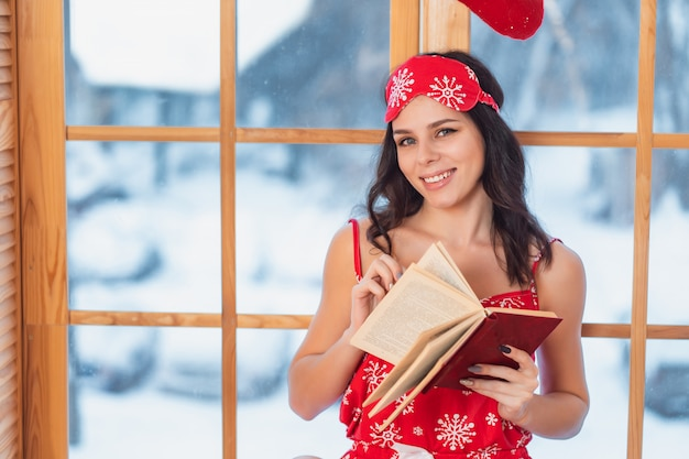 Bella giovane donna castana che indossa il pigiama rosso e che legge dalla finestra