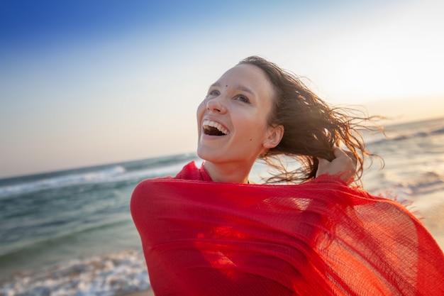 Bella giovane donna castana con capelli lunghi in un bikini con una sciarpa rossa luminosa in sue mani sull'oceano al tramonto