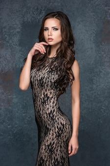 Bella giovane donna castana con i suoi capelli che posano in un vestito di trafori.