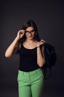 Bella giovane donna castana in vetri e pantaloni verdi con lo zaino