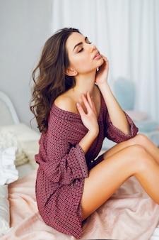 Bella giovane donna castana sexy che pone sul suo letto