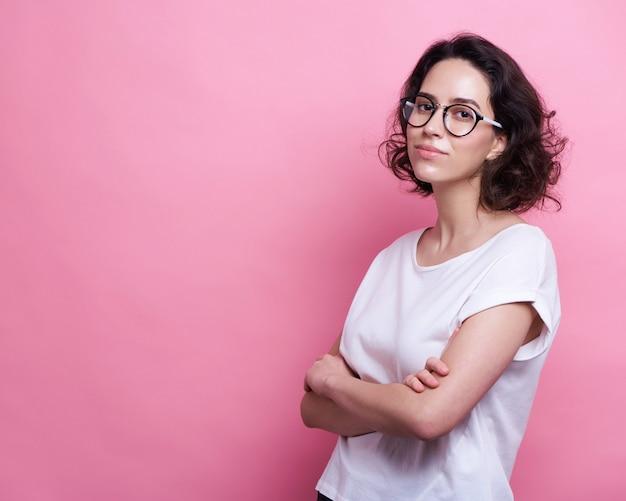 Bella giovane donna caucasica in occhiali rotondi trasparenti, mantiene la mano sollevata, vestita in abito casual,