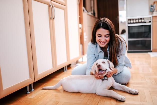 Bella giovane donna che accarezza il suo animale domestico mentre seduto sul pavimento a casa.