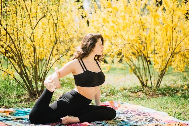 Bella giovane donna che allunga la sua gamba in giardino