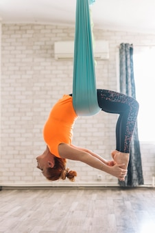 Bella giovane donna che appende sottosopra mentre praticando yoga aerea