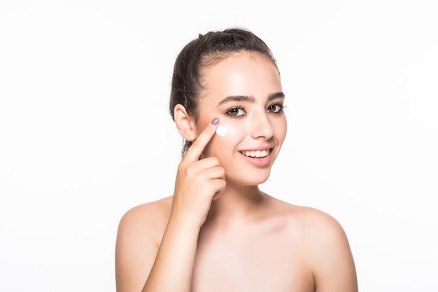 Bella giovane donna che applica cosmetico sotto gli occhi isolati sulla parete bianca