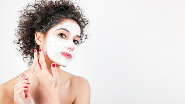 Bella giovane donna che applica crema cosmetica sul viso