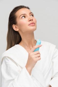 Bella giovane donna che applica la crema per la zona degli occhi