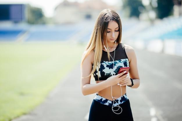 Bella giovane donna che ascolta la musica allo stadio