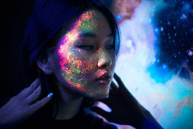 Bella giovane donna che balla e che fa festa con pittura fluorescente sul viso. ritratti facciali al neon