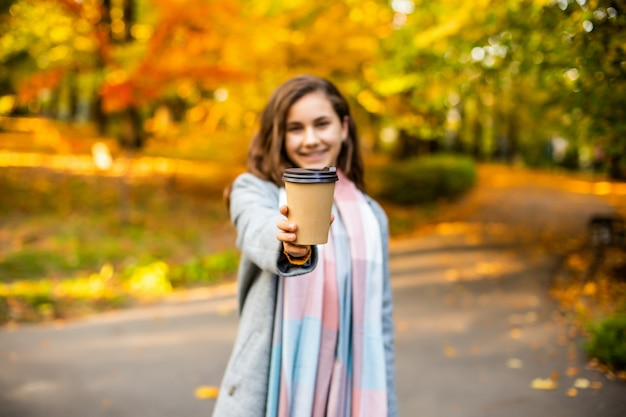 Bella giovane donna che beve caffè asportabile in parco in autunno.