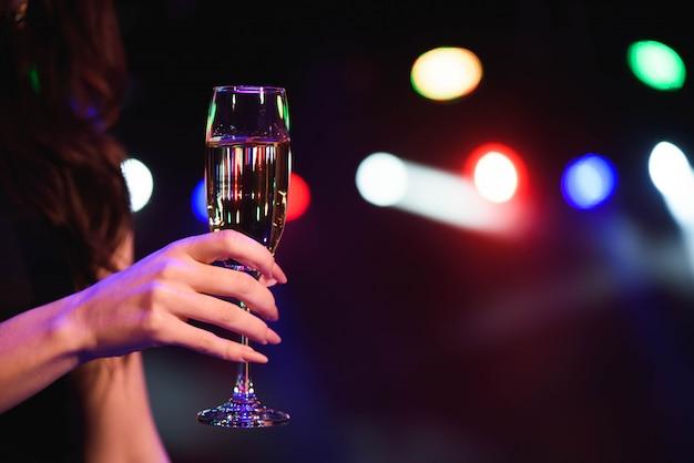 Bella giovane donna che beve champagne alla festa sopra le luci