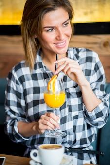 Bella giovane donna che beve il succo di arancia
