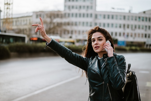 Bella giovane donna che cattura un taxi mentre parla su smartphone.
