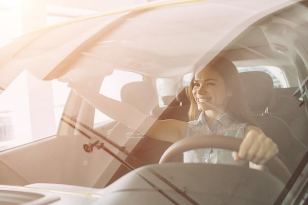Bella giovane donna che compra un'automobile alla concessionaria. seduta di modello femminile si siede nell'interno dell'automobile