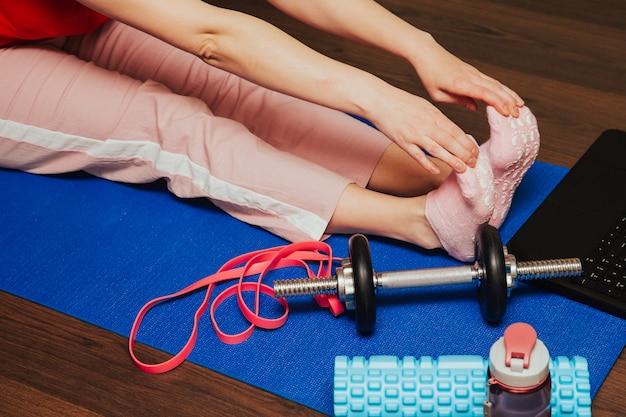 Bella giovane donna che fa allungando esercizio sul pavimento a casa, addestramento online sul computer portatile