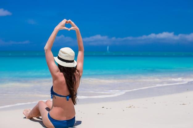 Bella giovane donna che fa un cuore con le mani sulla spiaggia