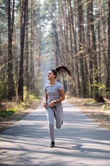 Bella giovane donna che funziona nel parco verde il giorno di estate soleggiato