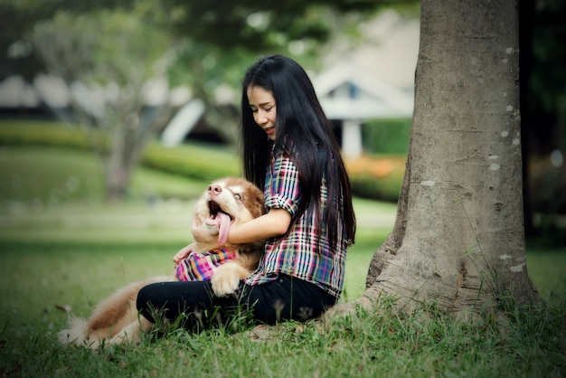 Bella giovane donna che gioca con il suo cagnolino in un parco all'aperto. ritratto di stile di vita.