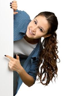 Bella giovane donna che giudica la carta in bianco dell'insegna isolata su superficie bianca