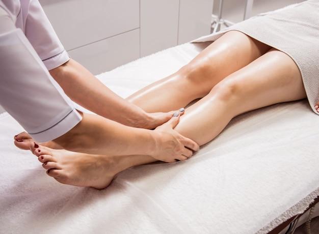 Bella giovane donna che gode del massaggio del piede nel salone della stazione termale. cosmetologia
