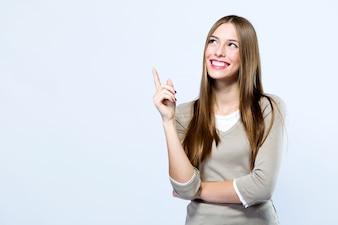 Bella giovane donna che indica in su sopra priorità bassa bianca.