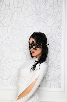 Bella giovane donna che indossa abito bianco e maschera in stile retrò moda