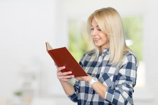 Bella giovane donna che legge e che tiene un libro
