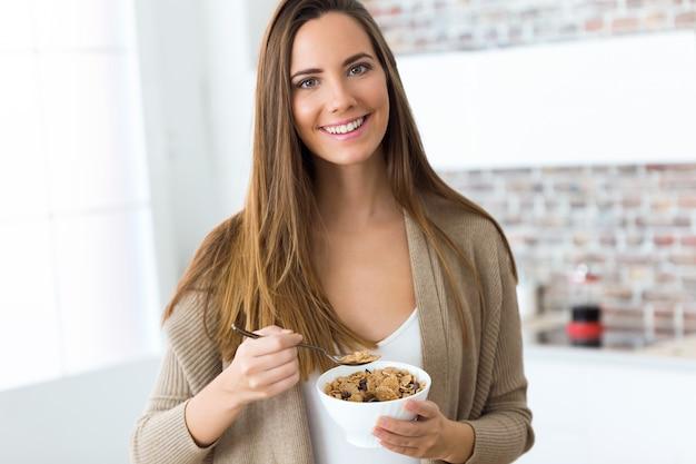Bella giovane donna che mangia i cereali a casa.