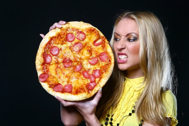 Bella giovane donna che mangia pizza