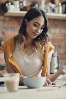 Bella giovane donna che mangia un'insalata sana e che legge una rivista