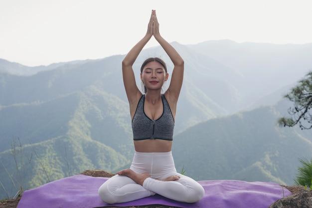 Bella giovane donna che medita e che si esercita sopra lui.