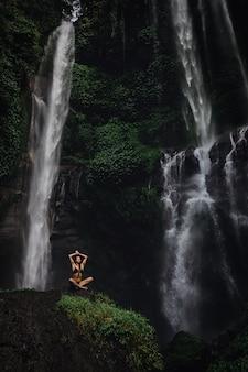 Bella giovane donna che medita nella posizione di loto mentre facendo yoga in una foresta meravigliosa vicino alla cascata. yoga femminile bello di pratica sulla roccia vicino alla cascata tropicale