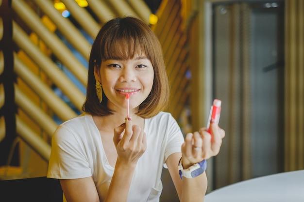 Bella giovane donna che mette sulla lucentezza rossa del rossetto.